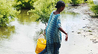 Woman carrying bucket of water