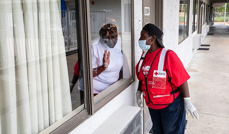 red cross employee looking through window