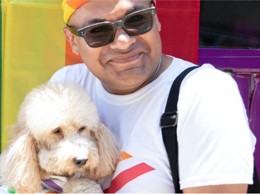 Man with dog in front of rainbow flag