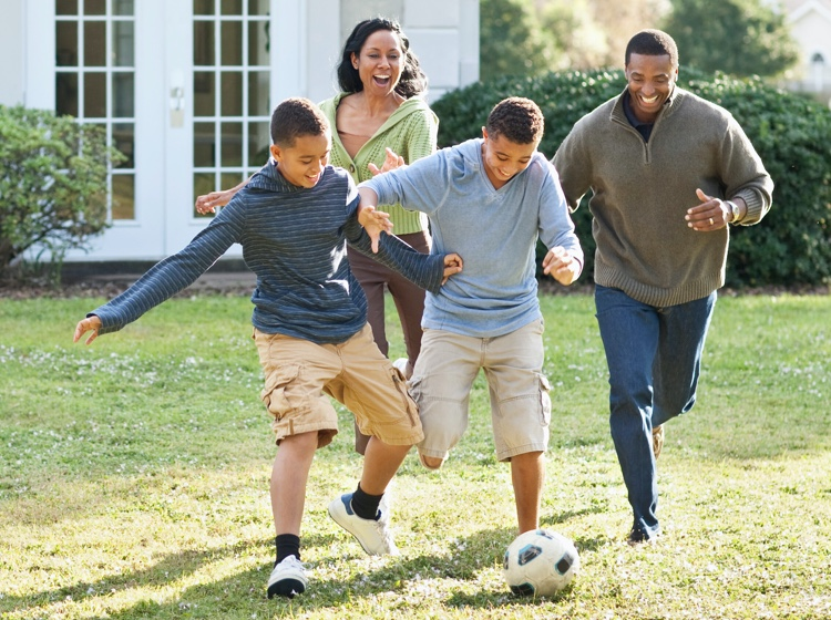 Family playing soccer in yard