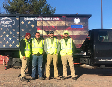 Four men standing in front of truck